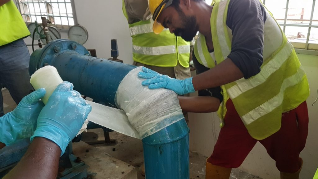 SylWrap HD Pipe Repair Bandage being applied to fix a pinhole leak in 150mm steel elbow joint
